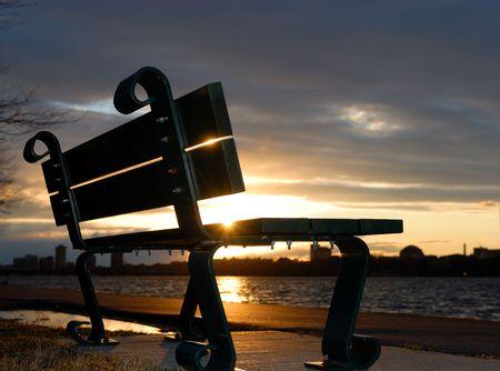 Empty bench backlit against sunset