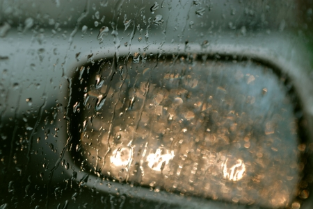 Droplets and car lights reflections on rear view mirror photo