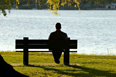 Young man sitting alone on park bench, looking down to the river in late afternoon