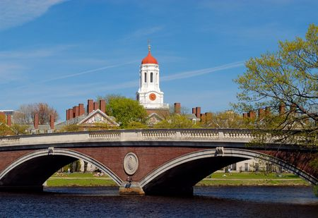 ivy league: Spring view of Harvard University Dunster Houses red dome and John W. Weeks Bridge in Cambridge, Massachusetts. Students relaxing on Charles River bank. Stock Photo