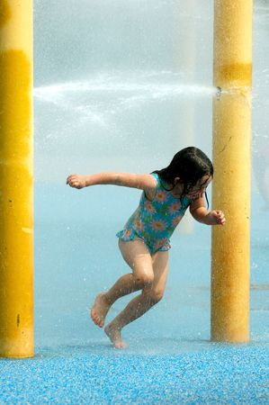 Girl playing in water sprinkler on summer day Stock Photo