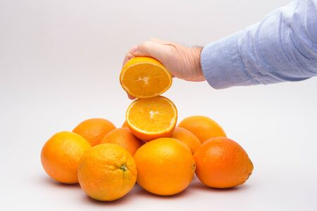 Orange is a fruit of a size that fits in the hand of an adult person, it is split in half to make a juice, rich in vitamins and low in calories; very refreshing Archivio Fotografico