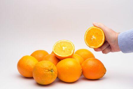 L'arancia è un frutto delle dimensioni che sta nella mano di una persona adulta, si divide a metà per fare un succo, ricco di vitamine e povero di calorie; molto rinfrescante Archivio Fotografico
