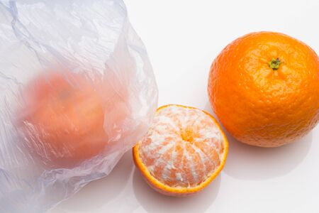 Plastic bag in which inside there is fruit, in this case mandarins; Almost transparent plastic bag to see that inside there is fresh fruit, bought in the supermarket to be able to move it home. Pollutant plastic