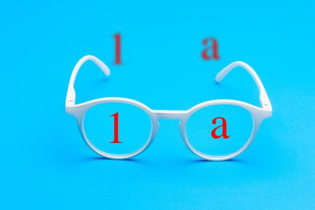 Glasses and lenses graduated on a plain background, with graduated glasses to be able to see either from far or near or to enlarge the size of the letters.