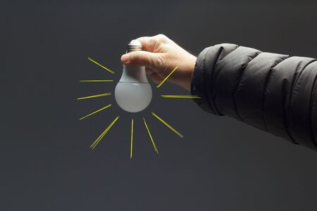 Energy saving daylight bulb, in the hand of an adult; bulb prepared to be installed and connected to electricity; It gives light and little heat.