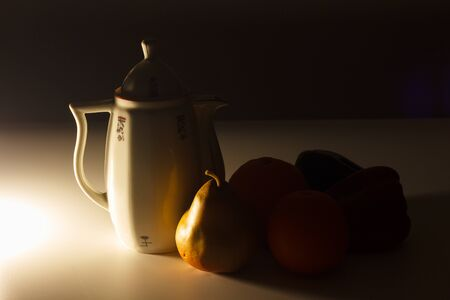 Vintage coffee maker with orange fruits, banana and red and green pepper. Classic minimalist still life with light, light and shadow proofs. 版權商用圖片
