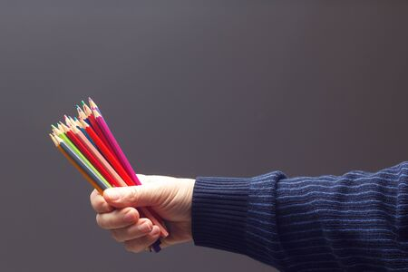 colors with the sharp point, group of colors united in the hand of an adult person; assorted colors in different pencils