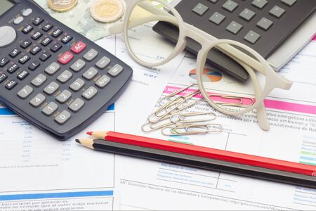 Papers, glasses and calculator to make calculations of the invoices we receive, to make graphs and statistics of our expenses or benefits. scientific calculator used by science students