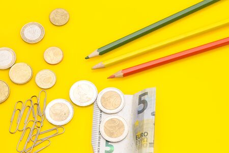 Diverse office supplies, clips, pencils, pen, staples, stapler, money, coins, compass; professional office or high school or university student office.