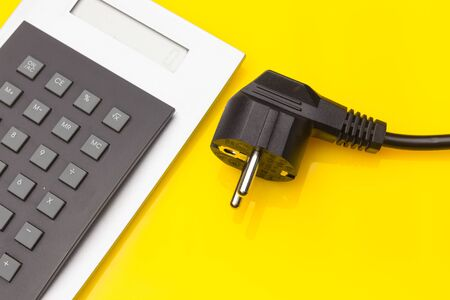 Electric plug with its metal terminals and protected with plastic to be isolated from electric current: Electric energy savings; saving money; Look carefully at electricity bills. Stock Photo