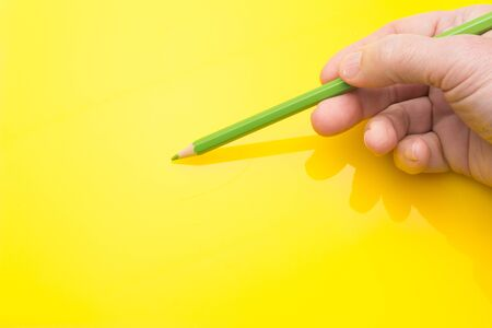 Wooden pencil with the interior of color and the exterior of the same color as in its interior, held in the hand of a person and on a colored background