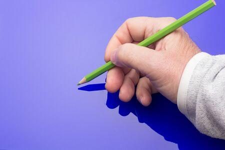 Lápiz de madera con el interior de color y el exterior del mismo color que en su interior, sostenido en la mano de una persona y sobre un fondo de color