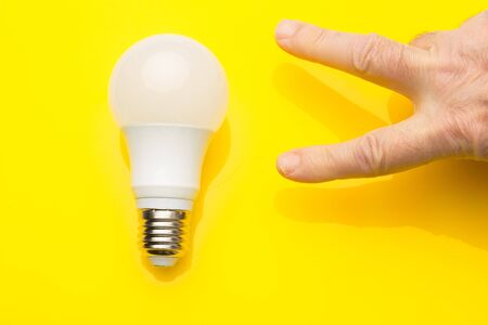 Low consumption, LED bulb, fluorescent, white color, daylight, efficient consumption and money saving; Energy saving light bulb, generates little heat and saves on electricity consumption. Archivio Fotografico