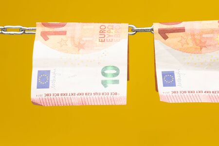 Money held in a chain or hung on a chain; paper money legal tender; Euros, currency of the European economic community, Common market. Reklamní fotografie