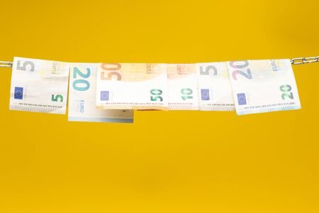 Money held in a chain or hung on a chain; paper money legal tender; Euros, currency of the European economic community, Common market. Banco de Imagens