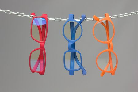 Colored glasses on a gray background and chain; glasses for vision correction; lenses to read or see from afar; Glasses can improve people's vision.