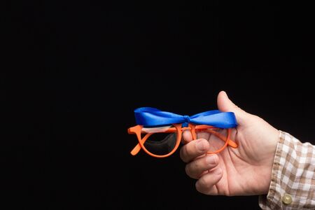 Visual health in the glasses, give away glasses for vision correction, colored designer glasses on a black background. Colored lenses in the hand of an adult person. Correction in the lenses of the glasses.