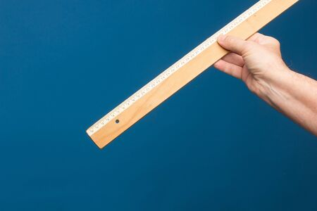 Wooden ruler in a person's hand, a classic vintage ruler of a lifetime.
