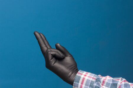Hygienic hand protection, fine black glove to avoid losing touch in the hands. Hand and finger signs. Фото со стока