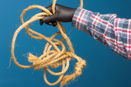 Yellow rope in the expert hand of an adult with protection. Thick rope to tie objects.