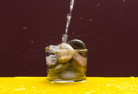 Transparent glass cup with stones inside and water splashing and throwing drops of water.