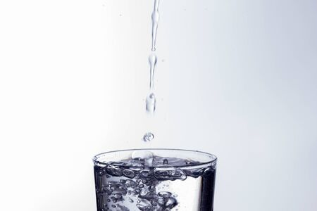Clear, drinking water falls into a clear glass, healthy, wholesome, fresh water with no odor or taste. Splash of water drops splashing onto the surface. Jet of water entering the glass