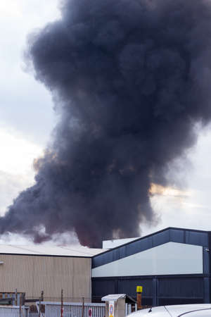 Firefighters, police, toilets, ambulances in a factory fire. Fire destroying a factory. 免版税图像
