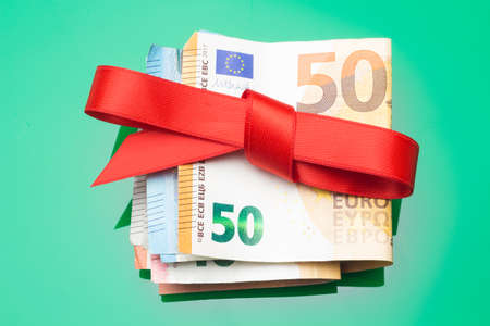Euro notes and coins decorated with gift bows; give away money at Christmas parties. When you don't know what to give, you give money. The best gift, give money and let everyone buy what they want.