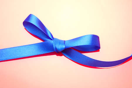 Colored bow for wrapping Christmas gifts or anniversary gifts: Pretty knot creating a gift bow on a bright colored fabric 免版税图像