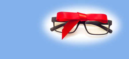 Glasses with graduated glasses and black frame, classic plastic on white background and red gift ribbon