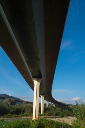 Motorway bridge seen from below, crossing a river; Pillars supporting the bridge, engineering work.