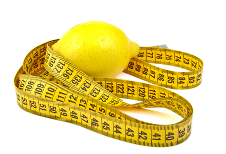 Lemon and tape measure on a bright background photo