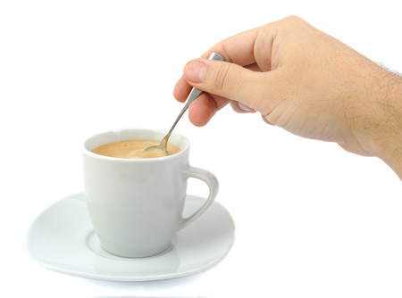Hand stirring a cup of coffee on a bright background photo