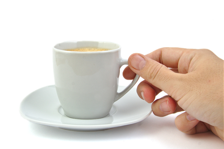 Hand and a cup of coffee on bright backgroud photo