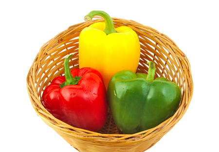 Green, red and yellow fresh peppers on a wicker basket isolated on white background photo