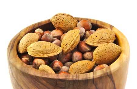 Almonds and nuts in a handmade wooden bowl isolated on white background photo