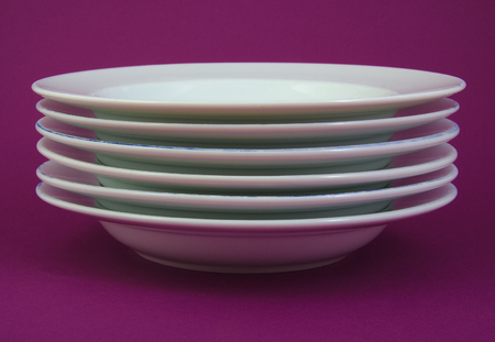 precarious: Stack of white and used dishes on purple background Stock Photo