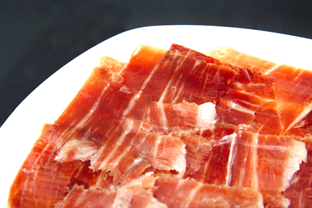 Closeup of serrano ham on black background. Spanish tapa. Foto de archivo