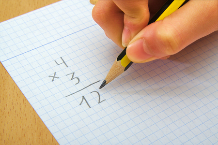 multiply: Closeup on the hands of a child doing maths. Multiply. School concept