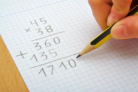 Hand van een kind het maken van een vermenigvuldiging met een potlood. Wiskunde. School concept Stockfoto