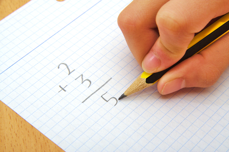 solving problem: Hand of a child making a sum. Math. School concept Stock Photo
