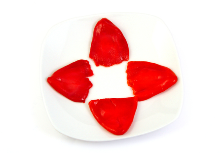 red skinned: Four roasted red peppers in olive oil on a white dish