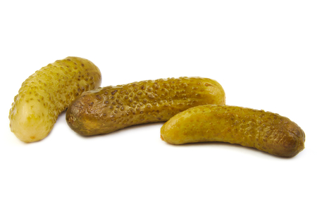 marinated gherkins: Three green pickles on a white background