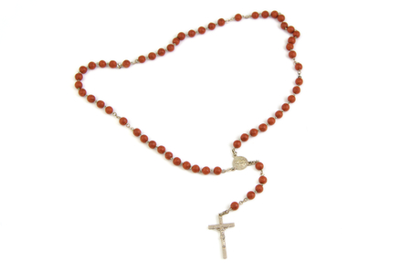 Wood rosary and metal cross with slightly unfocused beads isolated on white background