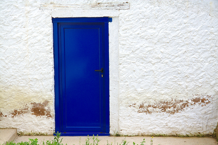 Old house white wall with a new blue door photo