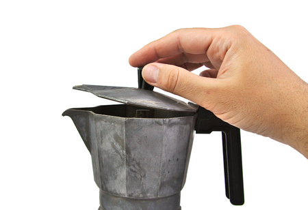 Caucasian man hand opening an old, used and rusty italian coffee maker isolated on a white background photo