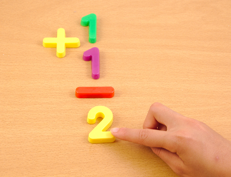 child studying: Child doing a sum with plastic items on the school wood desk Stock Photo