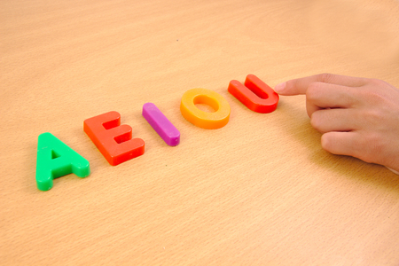 children learning: Letters a e i o and u and a child hand. School concept Stock Photo