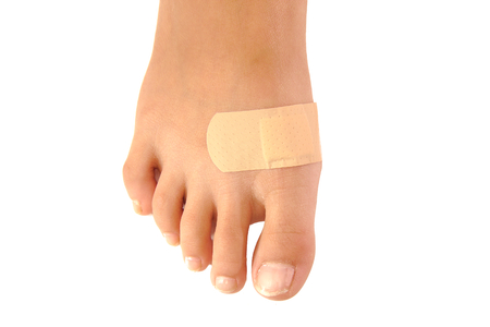 Close up of a band-aid on a foot isolated on white background Archivio Fotografico